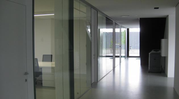 Ad Ultima (Kortrijk) - Glazen wanden in gelaagd glas tussen houten deurkaders